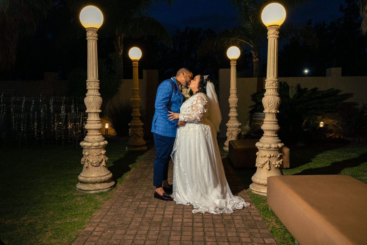 Landscape photo of bride and groom kissing after Reception, in a garden area with lights around them at the Milestone wedding venue in Port Elizabeth, photos taken by www.adamhendricksphotography.co.za, 8 of 8 photos.